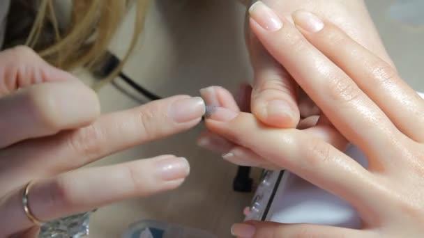Hřebík technik dává zákazníkovi manikúru na hřebík salon. Mladá žena přijímá francouzská manikúra.