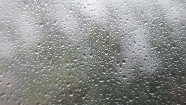 Kapky dešťové vody padají na okenní sklo