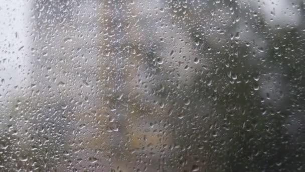 Esővíz cseppek hullanak az ablaküvegre.