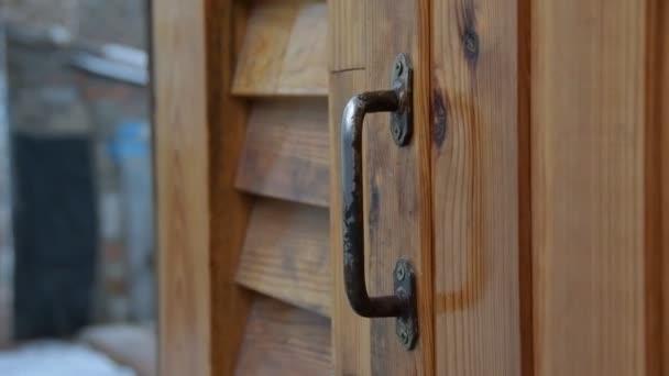 Dámská ruka otevírá dřevěné dveře