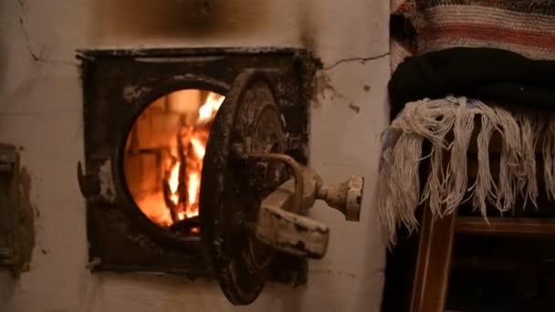 Rundhölzer brennen in einem Steinofen. Heiße Kohlen strahlen Wärme ab