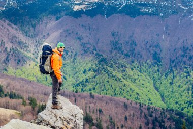 Man traveler standing on a mountain top. Forest background