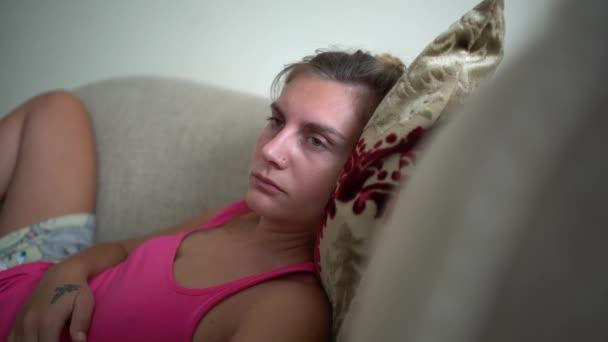Nő néz televízió visszajuttatásukra fekszik a kanapén