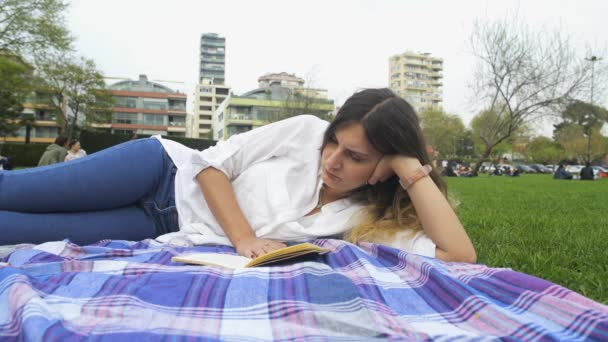 Young woman lying and reading a book in park