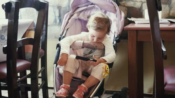 Cute little girl seating in the baby carriage, very tired and wants sleep.