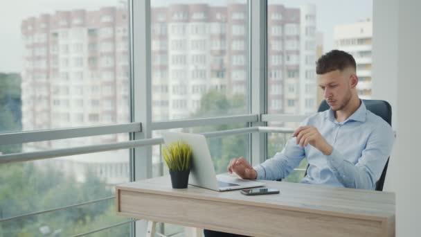 Mladý muž bělošského vzhledu, který pracuje u počítače. Muž se podívá na monitor počítače a má rád vzdálenou práci.