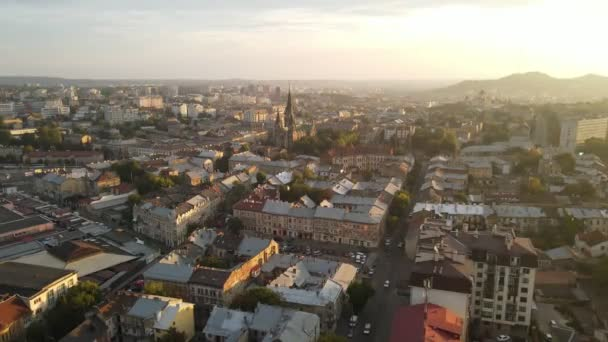 Aerial Flight on a fabulous city at sunrise. Morning in the small town of Lviv in Ukraine. The suns rays on the horizon fall on the houses. Warm light rays in the morning city.