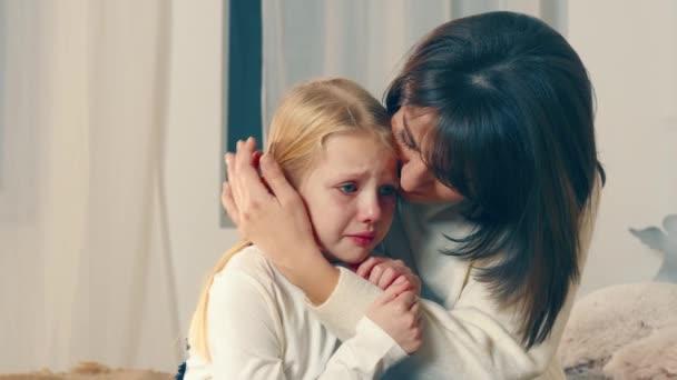 Máma uklidňuje svou dcerušku, která hodně pláče. Matky milují plačící dítě. Máma líbá svou holčičku. Hrubé dítě..