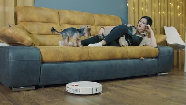 Frau ruht zu Hause auf der Couch und ein Staubsaugerroboter staubsaugt den Raum. Während der Roboter läuft, ruht sich die Frau aus. Die Zukunft in der Zimmerreinigung.