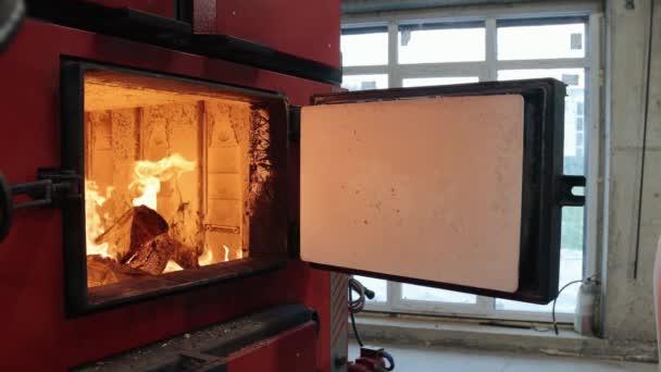 Heizraum auf umweltfreundlichem Brennstoff. Heizungswärter, der Holzstäbe in den Heizkessel wirft. Brennholz brennt im Ofen, Verbrennungsprozess, Hausheizung, Wintersaison