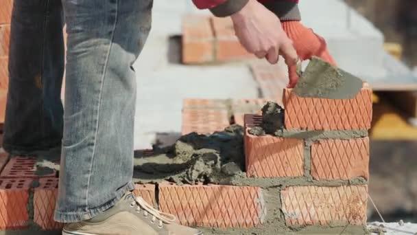 Blízko muže, který staví cihlový dům. Položit červené cihly na staveniště za slunečného dne. Dům výstavba close up.