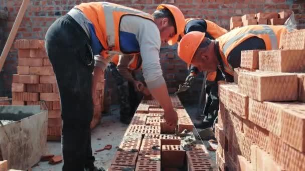 Stavbaři stavějí cihlovou zeď. Stavební práce na stavbě. Mistři položili cihly a postavili zeď domu..