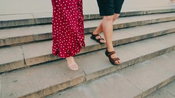 Legs of a man and a woman going down the stairs.