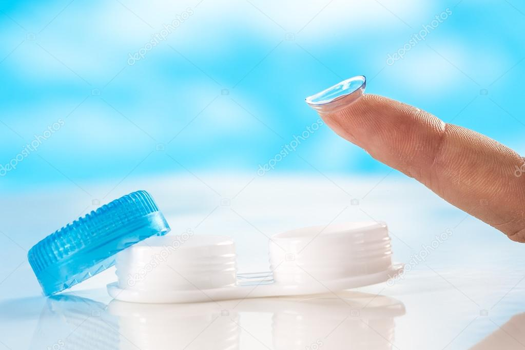 Contact lens on finger tip  blue background