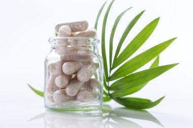 Herbal drug capsules in glass bottle with green l Alternative medicine concept.
