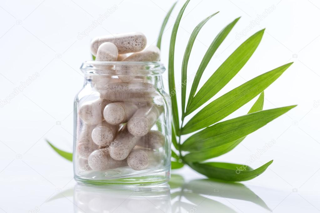 Herbal drug capsules in glass bottle with green l Alternative medicine concept.