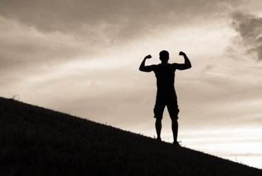 Male flexing on a hill.