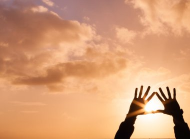Hands holding up a heart at sunset