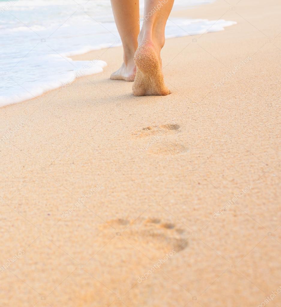 Woman walking on beach leaving footprints in the sand