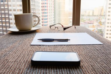 Working place with cup, phone, paper and glasses