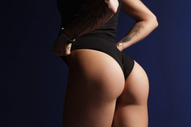 Sexy ass of a young girl  against a dark background