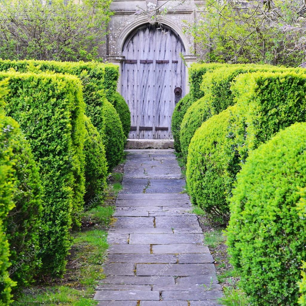 Stone Paved Topiary Lined Garden Path Leading to an Old Oak Doorway