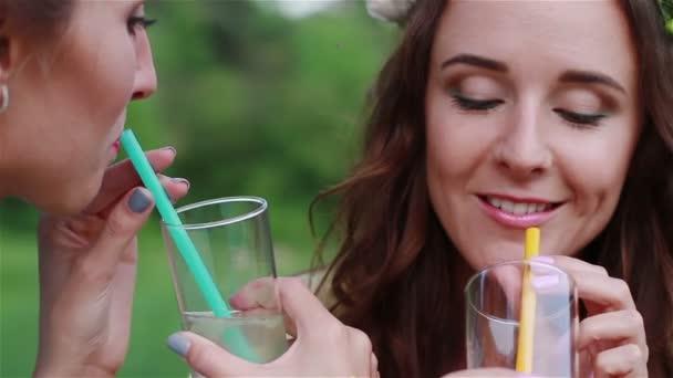 Beautiful girls kissing, drinking lemonade.