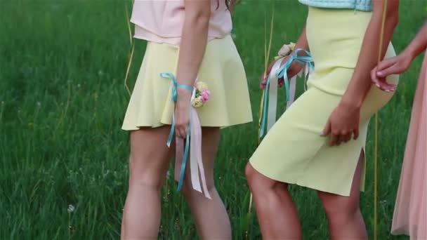 Krásné nohy tří dívek. Holky šaty a bílé tenisky na trávníku