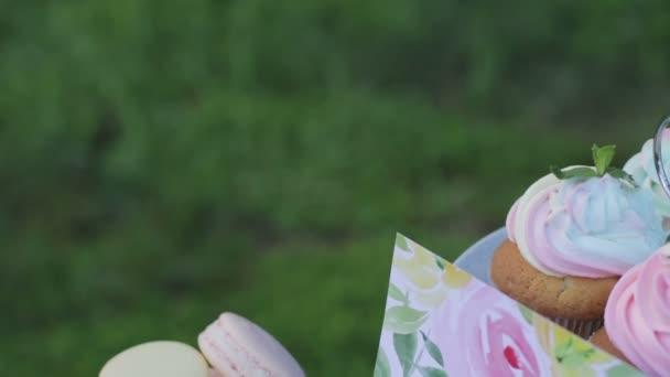 Dekor sladký tabulka. Prázdných sklenic s brčka. Bílý stůl s sladkosti na přírodu. Svatební dorty a květiny. Sladké kuličky. Bílý stůl a židle v přírodě