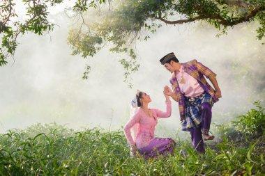Asian Muslim man and woman wearing traditional dress