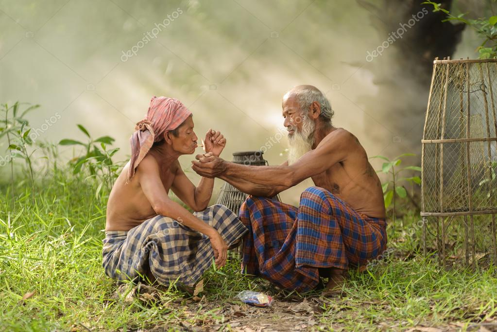 old man helps to  lighting a cigarette for another