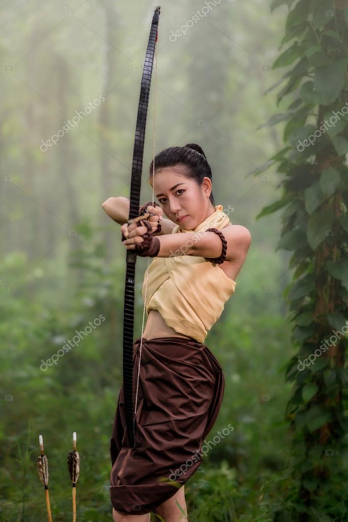 Beautiful archery woman aiming