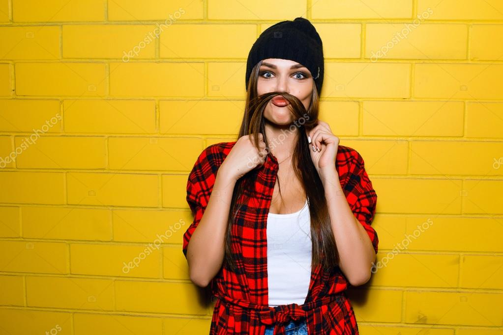9838385eb304be Beautiful young sexy hipster girl posing, smiling, do fake mustache near  urban yellow wall background in red plaid shirt, shorts, hat.– stock image