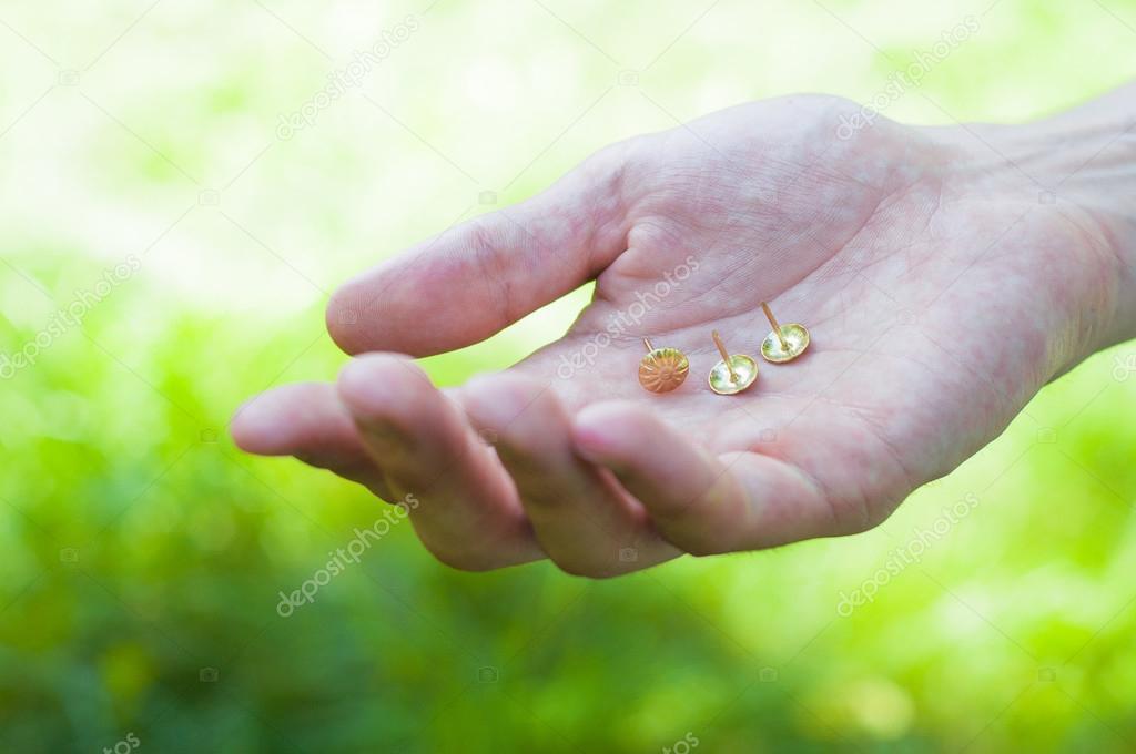 Tres pequeñas chinchetas en la mano masculina. Clavos dispersos con ...