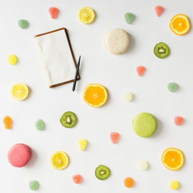 Colorful bright fruit pattern with notebook and sweets on white