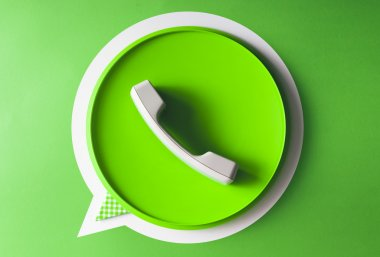 Green phone handset in speech bubble icon made of everyday objec