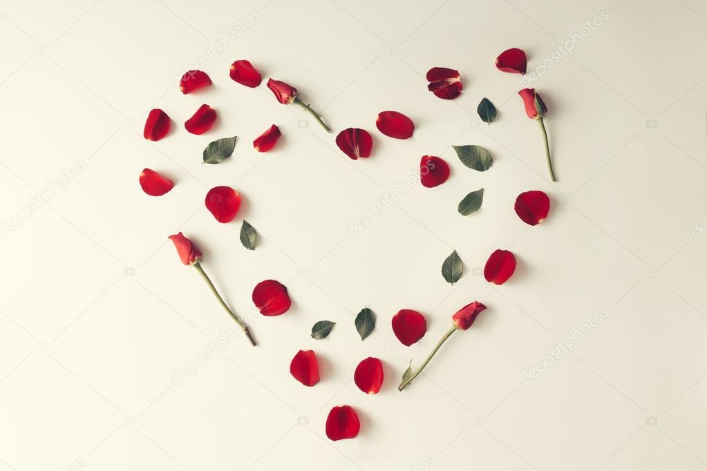 Red rose petal, leaves and flowers in a heart shape - Love conce