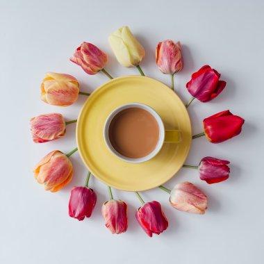 coffee with creative arrangement of tulip flowers.
