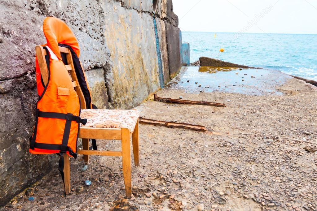 a life jacket on a chair against the sea