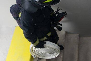 İtfaiyeci, elinde ekipmanla yanmayan merdivenlerden iniyor.