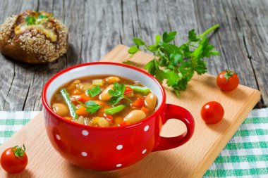 Minestrone vegetable soup with beans, cauliflower, tomatoes, close-up, top view