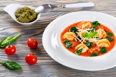 tortellini soup with italian sausages, spinach, tomato, parmesan cheese , pesto-sauce