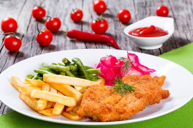 fried pork chop with french fries, green bean and salad