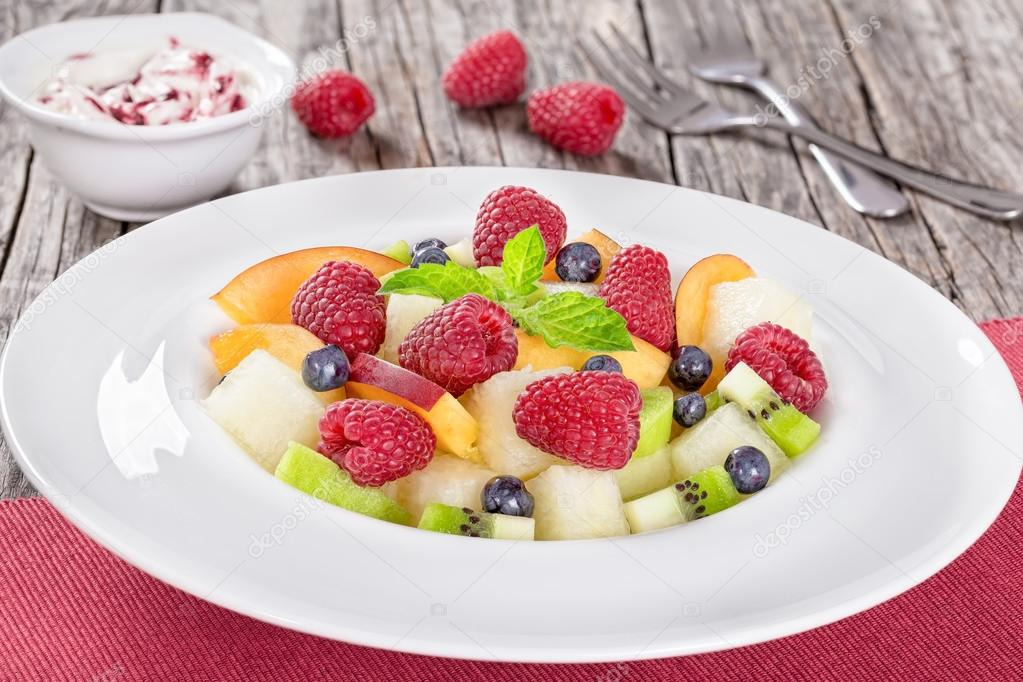 delicious fruit  and berry summer salad decorated with mint leav