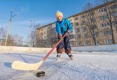 Usměvavý chlapec hraje lední hokej