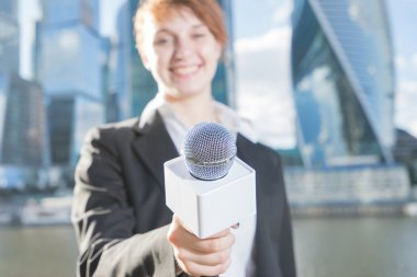 woman in business suit holding a microphone