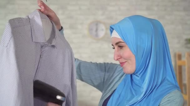 Muslim woman in national headscarf with a home steamer cleans clothes in the living room close up