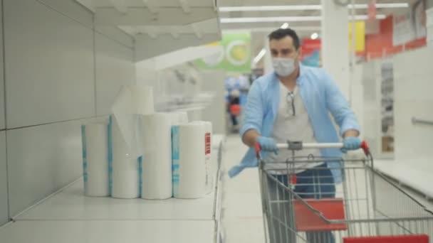 muž v masce a rukavicích kupuje toaletní papír v panice