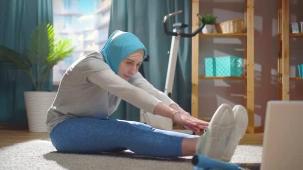 Gyönyörű fiatal muszlim nő egy nemzeti fejkendőben bemelegít egy laptop előtt.