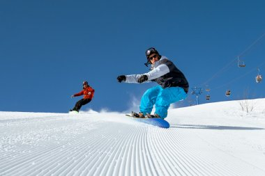Two snowboarder riding on ski slope